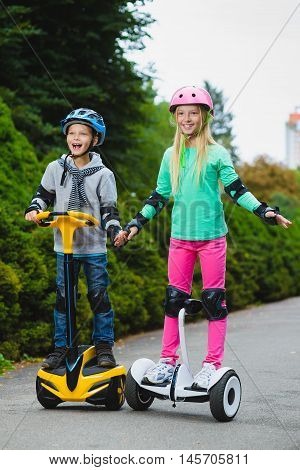 Happy kids riding on hoverboards and show thumbs up outdoor