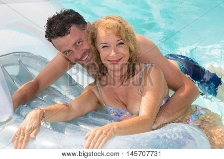 Cheerful Midlife Couple On Holiday In Swimming Pool