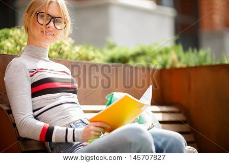 girl with notebooks sitting on bench in front of building