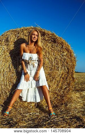 Lovely fashion woman near hay stack. Beauty romantic girl outdoors against hay stack. Photo of sexy blonde in a field with haystacks