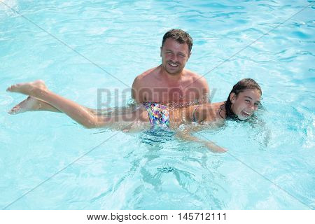 Little Girl Learning How To Swim With Swimming Instructor.