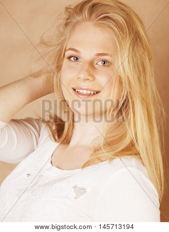 young cool blong teenage girl messed with her hair smiling close up