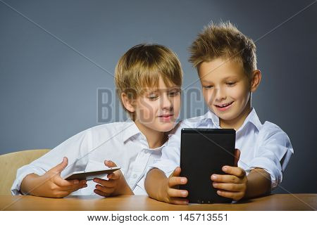 school concept. Smiling happy boys sitting at the desk and keep ebooks.