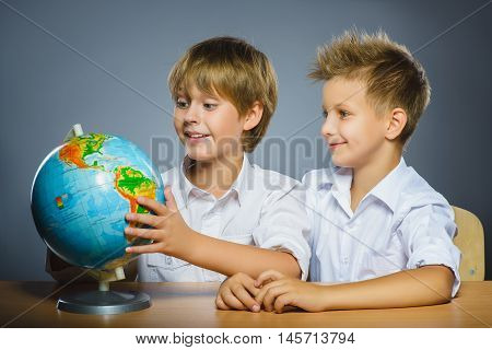 school concept. Smiling happy boys sitting at the desk and show at the Globe.