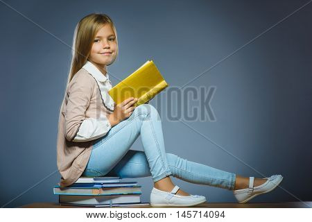 school concept. girl sitting on books and holding a book in hand.