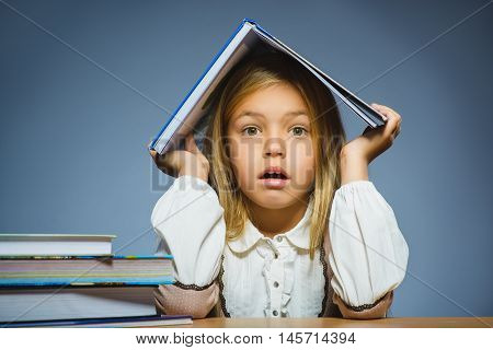 school concept. doubt girl sitting at desk and holding book on her head.