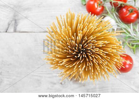 bunch of wholegrain spaghetti from above blurry background with tomatoes and herbs on rustic gray wood generous copy space closeup with selected focus and a very narrow depth of field