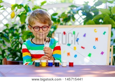 Funny adorable little kid boy with glasses holding lots of brushes and colorful watercolors. Happy child and student is back to school and looking at pupil's stuff on warm day.