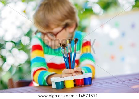 Frustrated little kid boy with glasses holding lots of brushes and colorful watercolors. Sad child and student is back to school and looking at pupil's stuff on warm day. Selective focus.