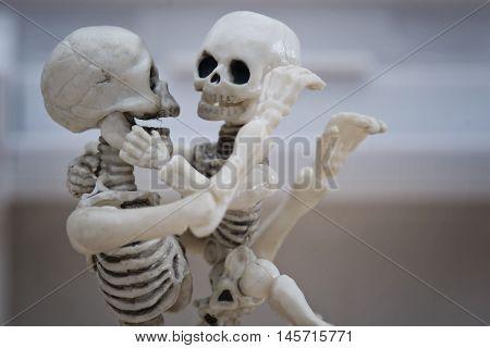 A skeleton parent hugging his skeleton kid