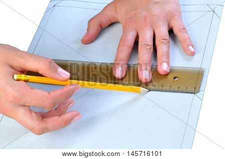 person making a template on textile hands close up.