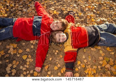 Two smiling boys lying down together on withered grass in autumn park