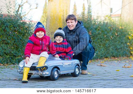 Two little kids boys in colorful clothes and happy dad driving old car. Father and sons making competition, outdoors. Active leisure for children on winter day