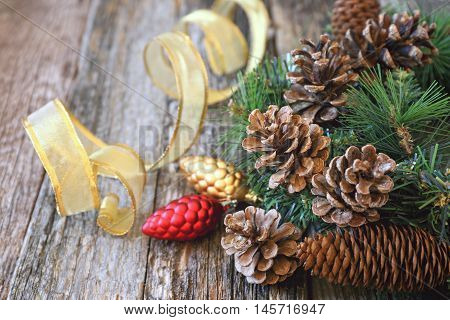 Pine cones and New-Year tree decorations on a wooden backgroundToned image