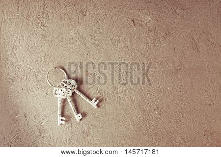 A bunch of vintage metal keys on ring hanging on the screw on the grey concrete background