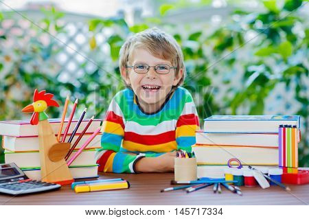 Cute beautiful little kid boy with glasses and lots of pupil's stuff like crayons pens, scissors and books. Child and student is back to school and happy about begin of lessons.