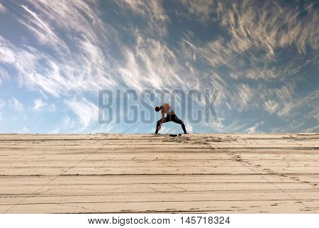 Young woman doing workout in the dune of a beach under beautiful clouds at dawn