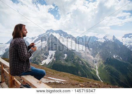 Man drinking hot tea on mountain, alpine view, snow on hills. Dombay, Karachay-Cherkessia, Caucasus, Russia.
