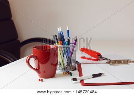Office desk with various items including coffee cup and stationary