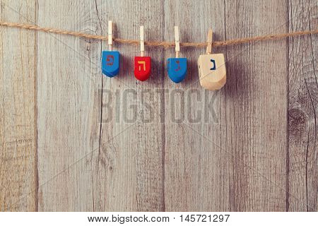 Jewish Holiday Hanukkah background with wooden dreidel spinning top hanging on string