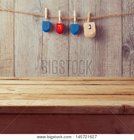 Empty wooden deck table with Hanukkah dreidel spinning top hanging on string