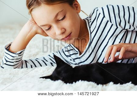 10 years old pre teen girl lying down on sofa and playing with black kitten