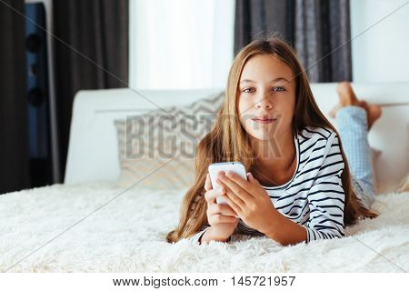 10 years old pre teen girl lying down on sofa and playing with smartphone
