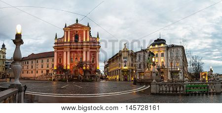 LJUBLJANA SLOVENIA - FEBRUARY 24 2016: Triple Bridge. Illuminated church and famous old buildings in the city center