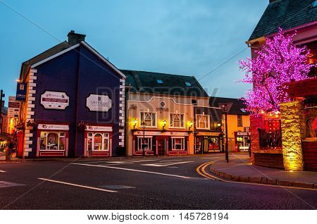 ENNIS IRELAND - SEPTEMBER 12 2014: Nightlife at the medieval old part of the popular touristic city in Mid-West Region. It hosts many restaurants and bars blurry people at the street