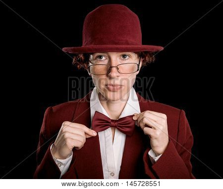 Strange person in red suit and bowler hat straightening bow tie.