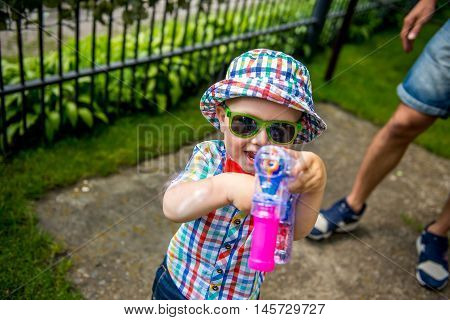 boy in a hat with a pistol for soap bubbles in summer.