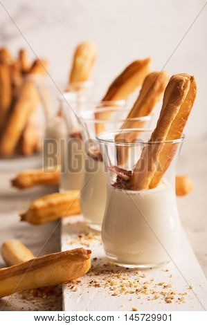 Sweet Tasty Eclair with white sauce. Small cakes into glasses with cream and chocolate chips