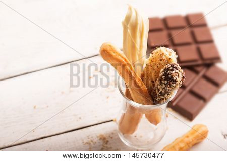 Sweet Tasty Eclair with white sauce. Small cakes into glasses with cream. Image with copy space
