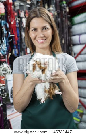 Happy Saleswoman Holding Guinea Pig At Store
