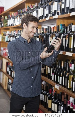 Customer Looking At Wine Bottle In Store