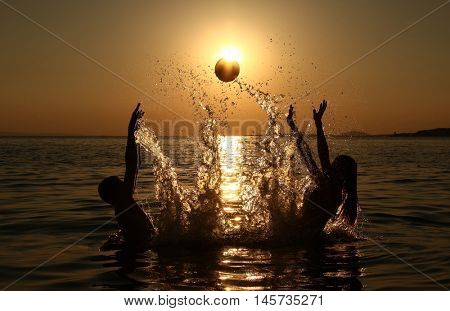 Young people are playing with ball on beach sunset