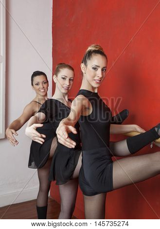Beautiful Young Ballerinas Stretching At Barre