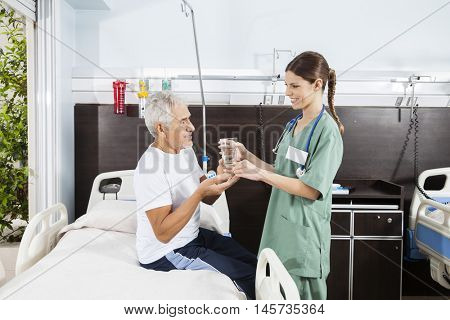 Nurse Giving Medicine And Water To Senior Patient