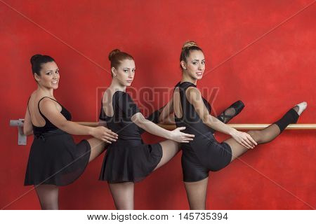 Confident Ballerinas Practicing At Barre Against Red Wall