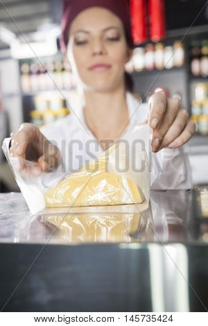Saleswoman Wrapping Cheese In Grocery Store