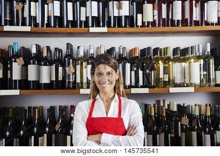 Happy Saleswoman Standing Against Shelves In Wine Shop