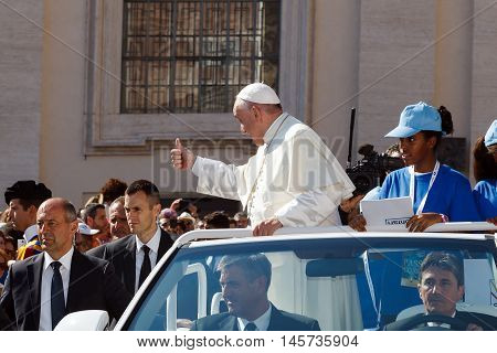 Vatican State - September 3, 2016: Pope Francis on the new convertible car, waving to the crowd of faithful gathered in St. Peter's Square for the sanctification of Mother Teresa of Calcutta. The car's margins men guarding the security that everything is