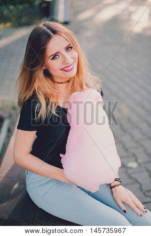 Young beautiful stylish girl sitting on the bench in park with cotton candy