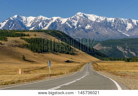 Scenic view with the asphalt road in the steppe going to the mountains with snowy peaks and slopes covered with forest on a sunny day