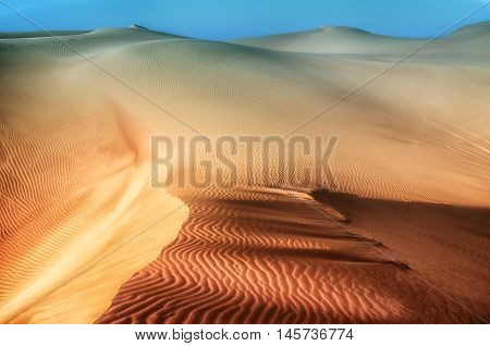 Dunes background.Arid desolate landscape.Footprints in the sand.Structure of waves in the sand.Dunes in the desert.
