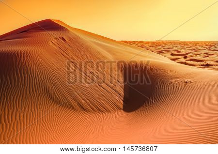 Dunes background.Arid desolate landscape.Sahara sunset.Footprints in the sand.Structure of waves in the sand.Dunes in the desert.Adventure trip to desert nature.