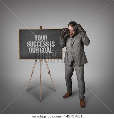 Your success is our goal text on blackboard with businessman with boxing gloves