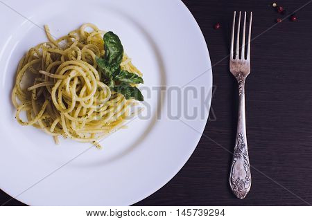 Close up italian pasta spaghetti with homemade green pesto sauce and basil leaf with a fork on dark background. Delicious healthy vegetarian food. Italian food concept. Top view.