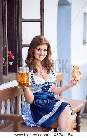 Beautiful young woman in traditional bavarian dress sitting on wooden bench holding a mug of beer and pretzel against old country house. Oktoberfest.