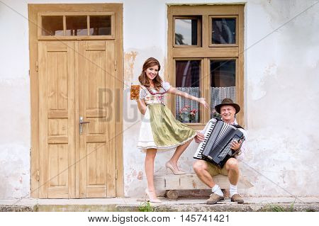 Couple in traditional bavarian clothes standing against old country house, man playing accordion, woman holding a mug of beer. Oktoberfest.